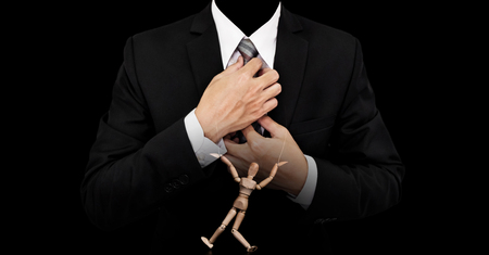 obedecer: El hombre de negocios con la figura marioneta de madera, el concepto de manipulación de negocio