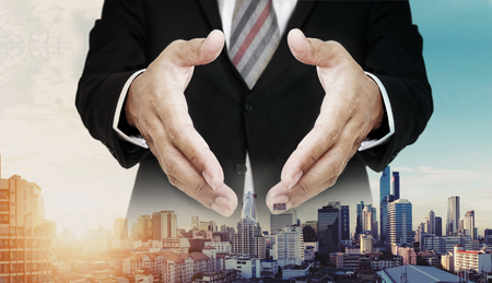 extending: Businessman extending hands with panoramic cityscape of Bangkok city in sunrise