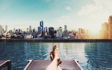 Relaxing in holidays, Panoramic feet on sun bathing bed at swimming pool on roof top in the city