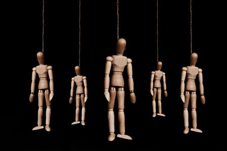 ahorcado: Bajo llave, grupo de marionetas de madera ahorcado marioneta por la cuerda, sobre fondo negro Foto de archivo
