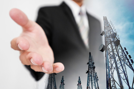 extending: Businessman extending hand, with double exposure Telecommunication towers with TV antennas and satellite dish