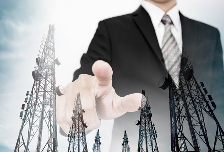 finer: Businessman pointing finer to screen with double exposure telecommunication electronic towers, business network
