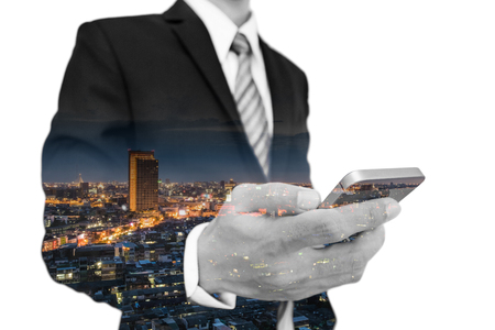 real leader: Businessman using smartphone with double exposure skyscraper cityscape
