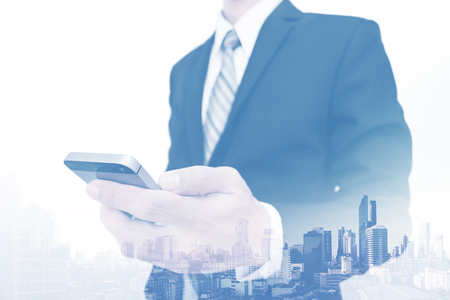 real leader: Double exposure businessman using smartphone with city view background Stock Photo