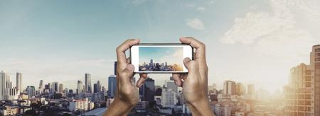 taking photo: Hand using smartphone taking photo of Bangkok city in sunrise