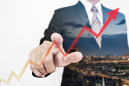 Businessman drawing a rising up arrow by finger, representing business growth Stock Photo