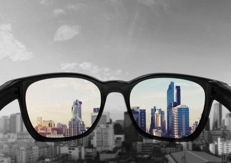 안경 렌즈에 초점을 맞춘 도시의 전망을 바라 보는 안경