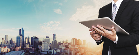 Businessman working on digital tablet outdoor, and city panoramic background Imagens