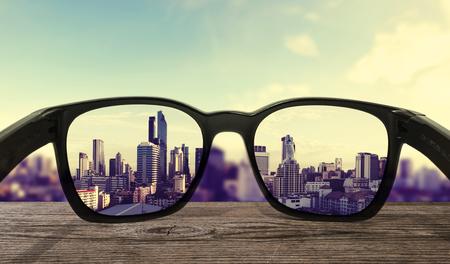 Sunglasses on wooden desk with city view background Foto de archivo