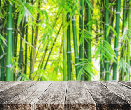 Wooden platform and Asian Bamboo forest with morning sunlight