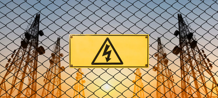 High Voltage Sign and Symbol Caution Signboard on Fence Wire at Electrical Power Plant Station in Sunset Imagens