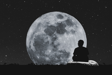 man on the moon: Silhouette a man sitting relaxing under full moon at night with stars on the sky