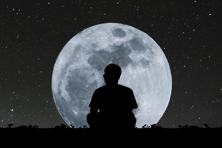 muted: Silhouette a man sitting relaxing under full moon at night with stars on the sky