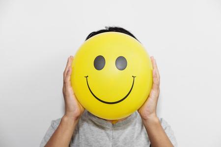 Un individuo que sostiene un globo amarillo con emoticon de la cara de la sonrisa en vez de la pista. Ocultando algunos malos sentimientos sólo mantener sonriendo Foto de archivo - 66407038