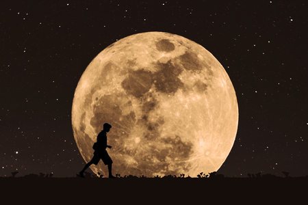 Silhouette a man walking under full moon at night with stars on the sky Stock Photo