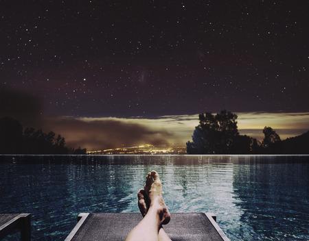 Relajarse en vacaciones, un hombre pies en la cama en la piscina de noche con luces de la ciudad y las estrellas en el cielo de fondo Foto de archivo - 66406948