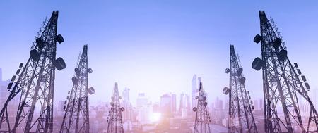 Silueta, torres de telecomunicaciones con antenas de TV y antena parabólica en la puesta de sol, con doble exposición de la ciudad en el amanecer de fondo
