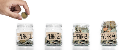 Money saving, Hand putting coin in glass jar with coins inside growing up, on white background Imagens