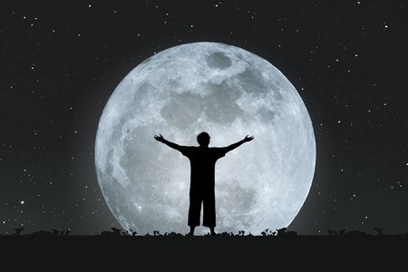 man on the moon: Silhouette a man stretching hands under full moon at night with stars on the sky Stock Photo