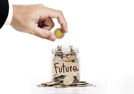 La mano puso la moneda en frasco de vidrio, el ahorro de dinero para el futuro, en el fondo blanco