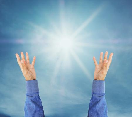 Hand versucht, auf den Himmel mit Sonnenschein Strahlen zu erreichen