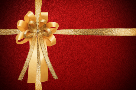 Golden ribbon with bow, on red leather paper texture, wrap gift box Stock Photo