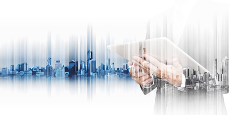 Businessman working on digital tablet with double exposure city, concepts of business communication technology Standard-Bild