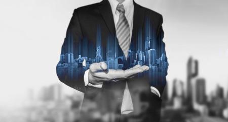 一方で、黒と白の街背景と青の近代的な建物のホログラムを保持している実業家 写真素材