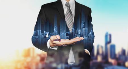 Unternehmer, die blau modernen Gebäuden auf der Hand Hologramm, mit der Stadt Hintergrund