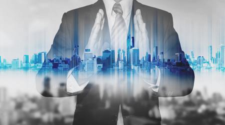 Double exposure businessman holding blue city hologram, real estate business technology