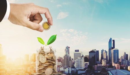 Saving money concepts, businessman hand putting coin in glass jar container, with plant bud glowing, on Bangkok city in sunrise background Banque d'images