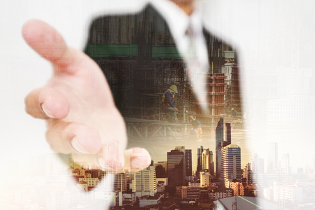 Businessman stretch out hand, with double exposure city and real estate site construction with workers