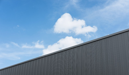 Corrugated factory industry wall on blue sky with clouds Banco de Imagens
