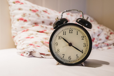 minuet: Retro alarm clock with 10 Oclock and twenty minuet, on white bed with pillow