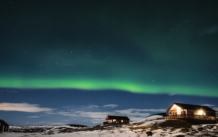 Aurora Borealis with cottage houses in winter
