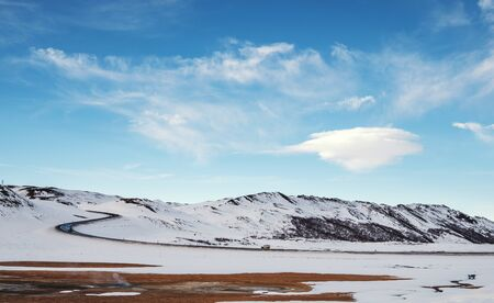 lenticular: Landscaped in winter with country road and lenticular cloud on blue sky