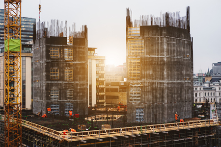 Site construction in the city with workers working in sunrise Stock Photo