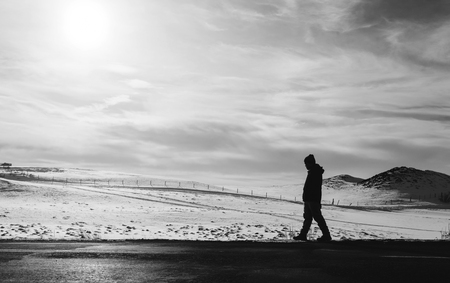 a man walking away on an empty desolated road Imagens