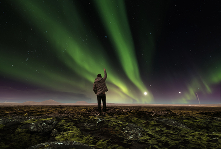 landscape of amazing beautiful  natural phenomenon Aurora Borealis, with a man raising arm , traveling in Iceland