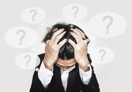 psychopathy: Businessman touching his head, with question marks sign on speech bubbles. doubt, problems, syndrome and disorder concepts