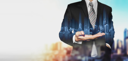 Businessman holding blue hologram of modern buildings, with blur background and copy space Stock Photo
