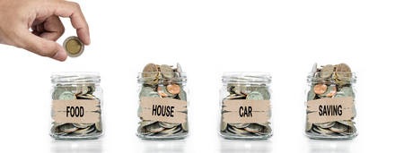 allocate: Hand putting coin in glass jar. Allocate money for foods, house, car and savings. Save money concept