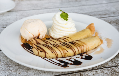 gateau: Banana crepes with vanilla ice cream and home made whip creme, glaze with chocolate and honey , selective focus Stock Photo