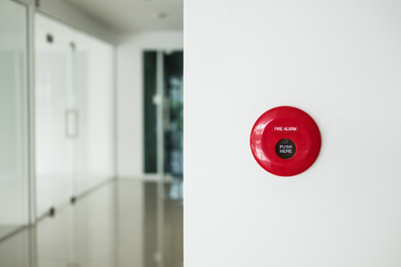 Fire alarm, emergency button on white wall in modern office