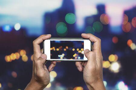 Prendre une photo par téléphone intelligent, mains tenant un smartphone prenant des lumières Bokeh Banque d'images - 83483797
