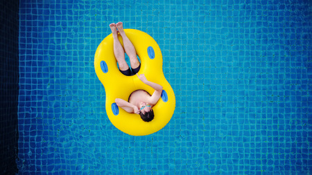 Top view, a man relaxing on yellow swim pool float, on swimming pool in summer