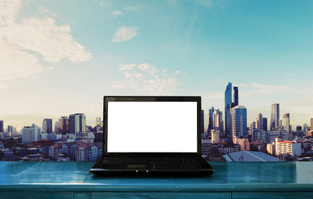 working: Laptop computer blank white screen on wood table with Bangkok cityscape background Stock Photo