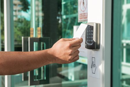 Hand using security key card scanning to open the door to entering private building. Home and building security system Banco de Imagens - 87803860
