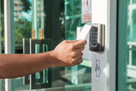 Mão usando a digitalização de cartão de chave de segurança para abrir a porta para entrar em edifícios particulares. Sistema de segurança residencial e predial