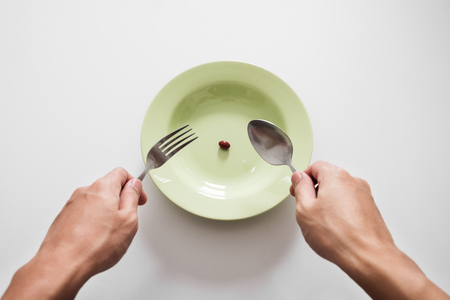 Supplementary food on the dish with fork and spoon on white table Stock Photo